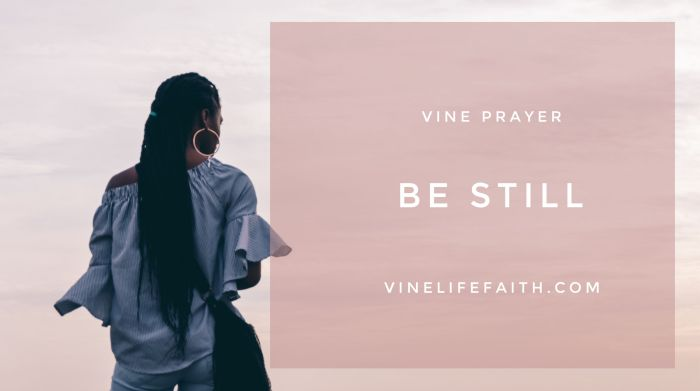 Woman of color alone, looking off into the sunset with text vine prayer, be still, vinelifefaith.com.